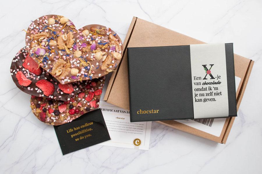 Een foto van het totaalpakket dat je ontvangt bij chocstar bestaande uit chocolade, een giftbox een persoonlijke boodschap.