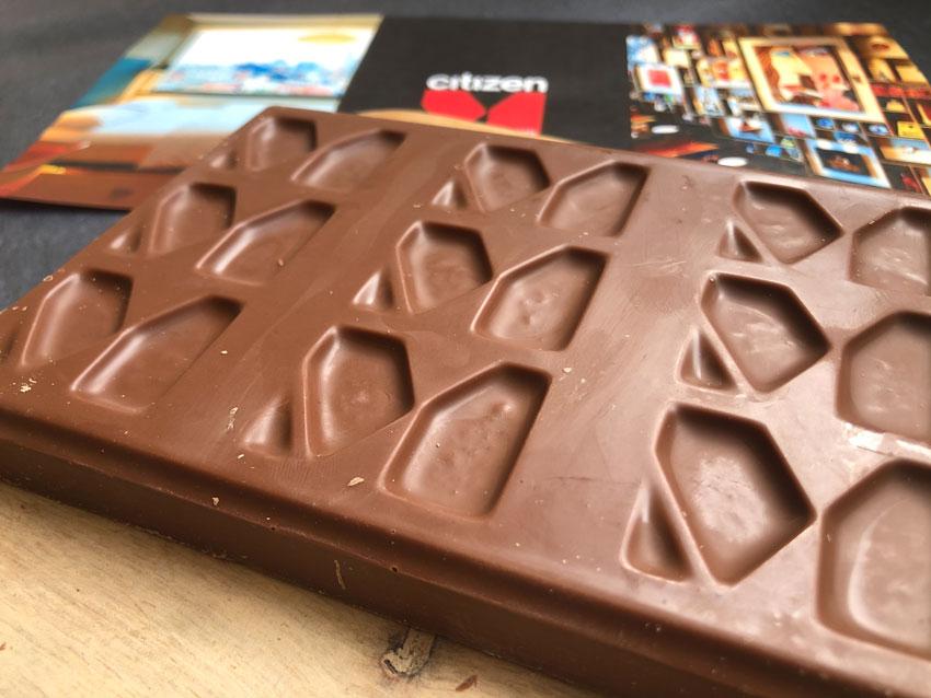 Een closeup van een gepersonaliseerde chocoladereep met het logo van Hotel Citizen M in meervoud in de chocoladereep verzonken